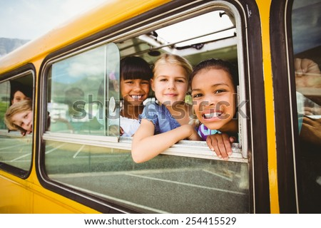 Cute pupils smiling at camera in the school bus outside the elementary school