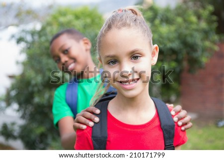 Cute pupils smiling at camera outside at the elementary school - stock photo