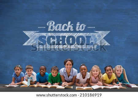 Cute pupils smiling at camera with teacher against blue chalkboard with back to school message - stock photo