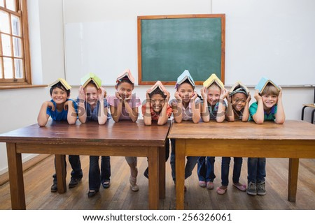 Cute pupils smiling in classroom at the elementary school - stock photo