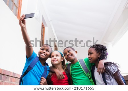 Cute pupils taking a selfie in the corridor at the elementary school - stock photo