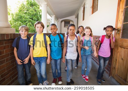 Cute pupils walking down the hall at the elementary school - stock photo