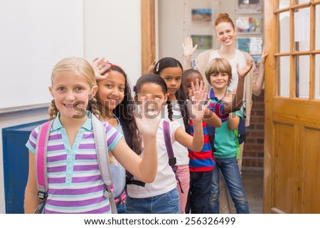 Cute pupils waving at camera in classroom at the elementary school - stock photo