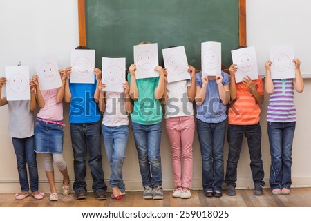 Cute pupils with funny faces in classroom at the elementary school - stock photo