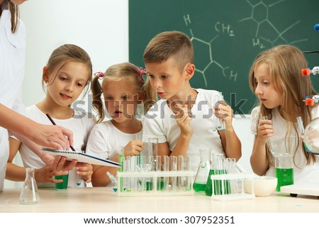 Cute pupils with teacher doing biochemistry research in chemistry class - stock photo