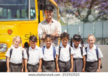 Cute pupils with their school bus driver outside the elementary school