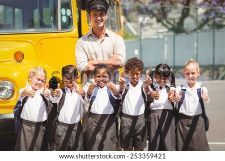 Cute pupils with their school bus driver outside the elementary school - stock photo