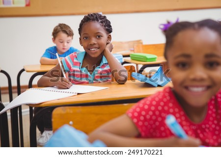 Cute pupils writing at desk in classroom at the elementary school
