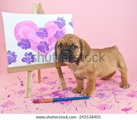 Cute puppy standing with a painting of a heart with paw prints going through it.