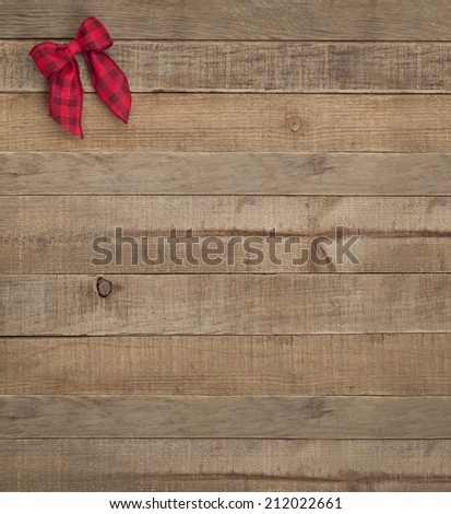 Cute Red Checked Christmas Bow in Upper Corner on Rustic Wood Board Background with Room or space for copy, text, words.  Country style barn look vertical that can be cropped to horizontal - stock photo