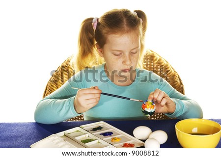 cute red haired girl is painting easter eggs