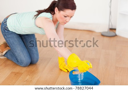 Cute red-haired woman cleaning the floor while kneeling at home - stock photo