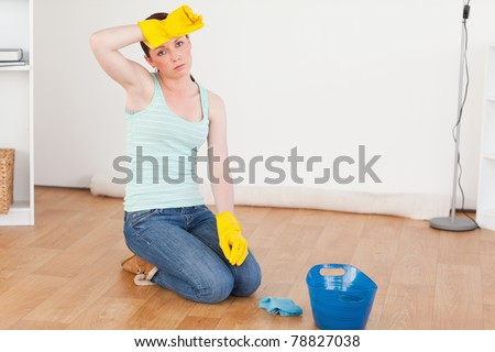 Cute red-haired woman having a break while cleaning the floor at home - stock photo