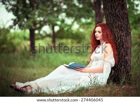 Cute red-haired woman sitting under the tree and reading a book - stock photo