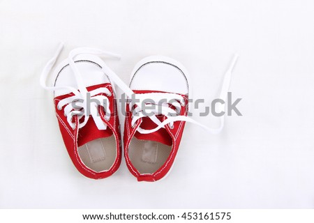 Cute red small sized canvas shoes top view on white background with copyspace - stock photo