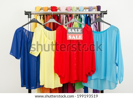 Cute red, yellow, blue blouses displayed on hangers with the sale sign. Rack with colorful summer clothes and accessories on clearance. - stock photo