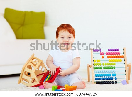 cute redhead baby playing with wooden toys, numerals, learning to count