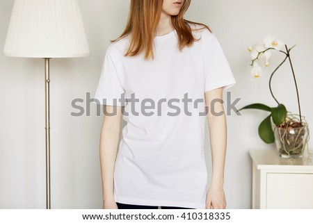 Cute redhead Caucasian teenage girl, cropped portrait. Young attractive female posing against home interior background, wearing white T-shirt with blank space for your message or advertising content   - stock photo
