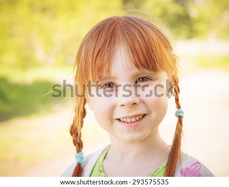 Cute redhead little girl on the meadow in summer day.