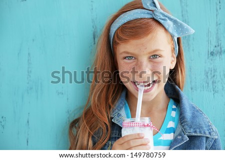 Cute redheaded child drinking milk on vintage blue background - stock photo