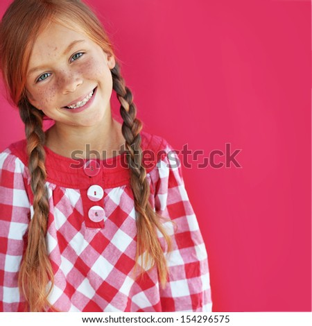 Cute redheaded child on red background - stock photo