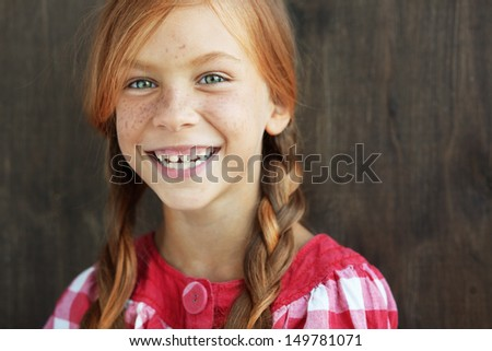 Cute redheaded child on vintage brown background - stock photo