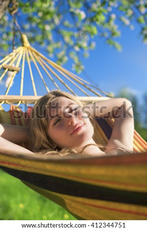 Cute Relaxing Caucasian Lady Resting in Hummock and Dreaming Outdoors.Vertical Shot - stock photo