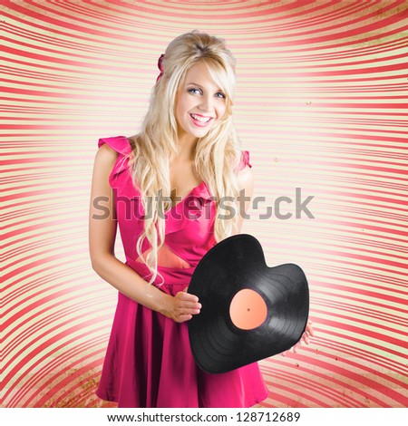 Cute Retro DJ Girl Holding Vintage Vinyl Record In The Shape Of A Heart When Rocking Out At An Old-Fashioned Disco In A Music Love Concept - stock photo