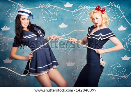 Cute retro portrait of two beautiful navy pinup girls wearing sailor uniforms pulling on a tug of war rope when personal training for elite fitness. Anchor and boat design background - stock photo