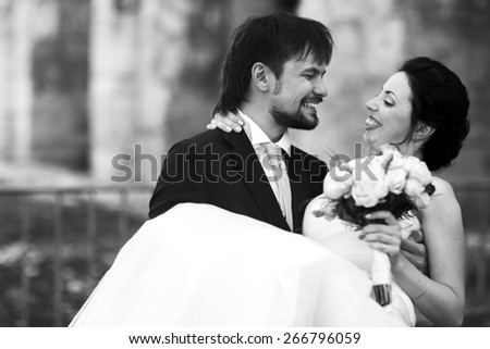 cute rich happy groom holds a bride smiling sunny Rome smiling and look at each other black and white