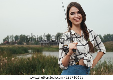 Cute rural brown haired lady posing against ranch house and pond with fishing rod. She stands in grass against rural scape. She wears jeans dress.   - stock photo