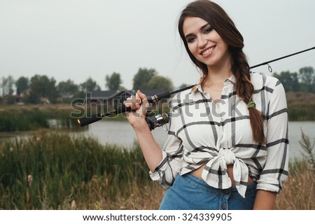 Cute rural brown haired lady posing against ranch house and pond with fishing rod. She stands in grass against rural scape. She wears jeans dress. House is made of wood and is brown. Fish-rod is black - stock photo