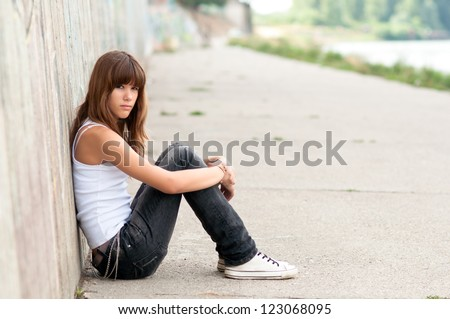 Cute sad teenage girl sitting alone in urban environment. - stock photo