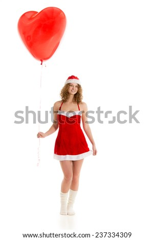 Cute santa girl in short red xmas dress and santa claus hat with giant heart shaped balloon full length - stock photo