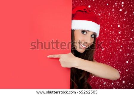 cute santa girl peeping over blank billboard while snowing - stock photo