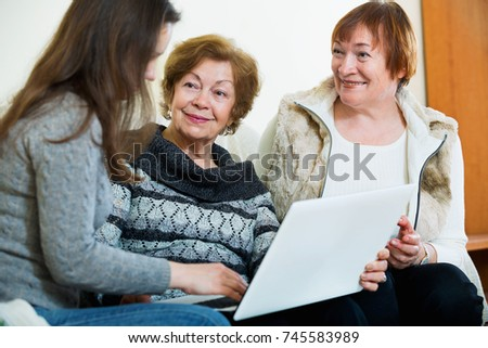 Cute satisfied girl teaching positive senior women using laptop in domestic