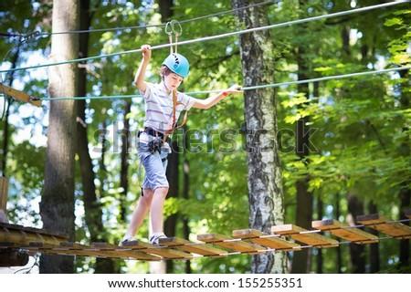 Cute school boy enjoying a sunny day in a climbing adventure activity park - stock photo