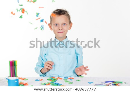 Cute school boy playing with letters - stock photo