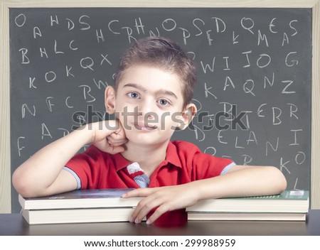 Cute school boy posing in front of a blackboard - stock photo