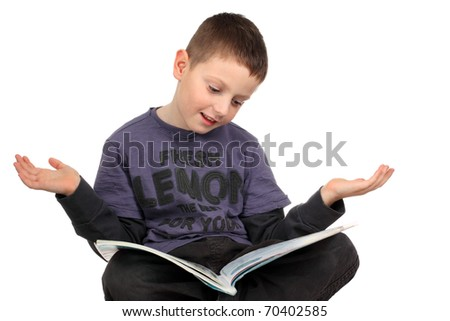 Cute school boy sitting on the desk and reading a book - stock photo