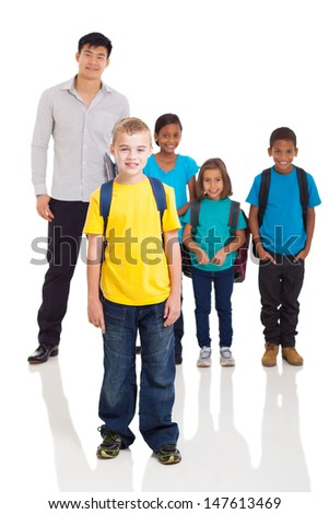 cute school boy standing in front of classmates and teacher on white background - stock photo