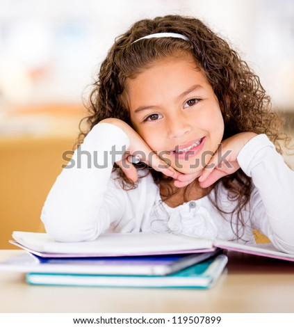 Cute school girl doing her homework and looking happy - stock photo