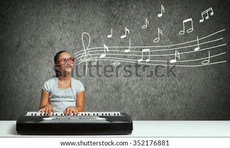 Cute school girl in red glasses playing piano - stock photo