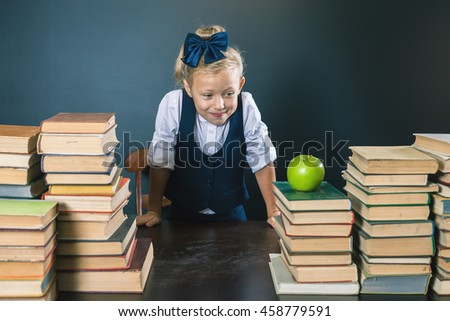 Cute school girl standing near the table with many books and looking at one green apple. Healthy nutrition, fruit. Blackboard. Student. Concept of education. The book - is knowledge.