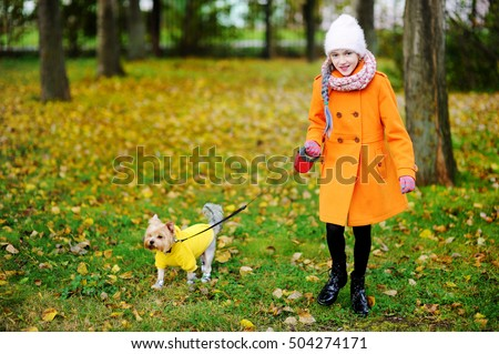 Cute schoolaged kid girl in orange coat walking with Yorkshire Terrier in the autumn park