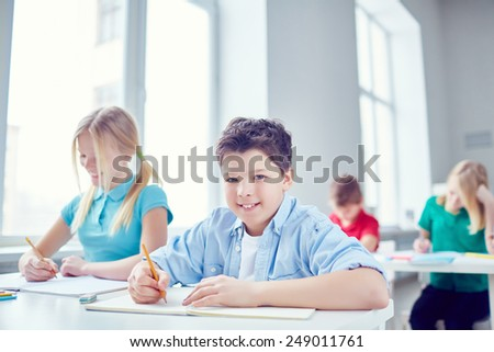 Cute schoolboy and his classmates working at lesson  - stock photo