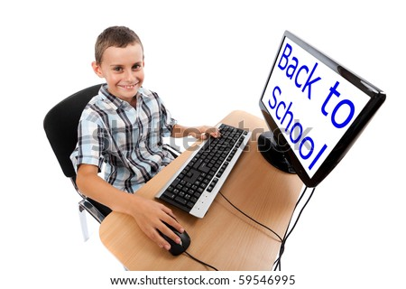 Cute schoolboy at his computer. The monitor can be used as copyspace - stock photo