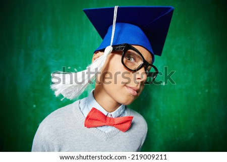 Cute schoolboy in eyeglasses and graduation hat looking at camera - stock photo