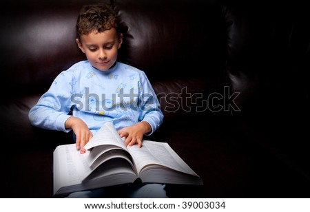 Cute schoolboy in pajamas reading a book (a dictionary) while sitting on a sofa