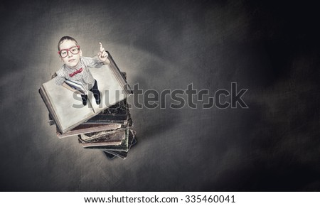 Cute schoolboy in red glasses with finger pointing up - stock photo